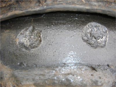 This image shows a closeup of AC interference induced corrosion, which appears as round craters in the pipeline coating.